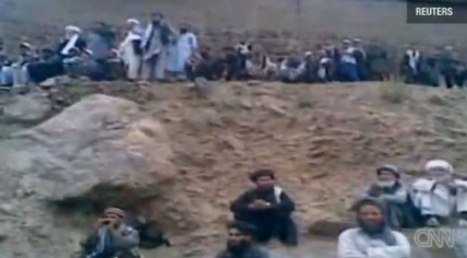 Dozens of men cheer at the execution of an Afghan woman